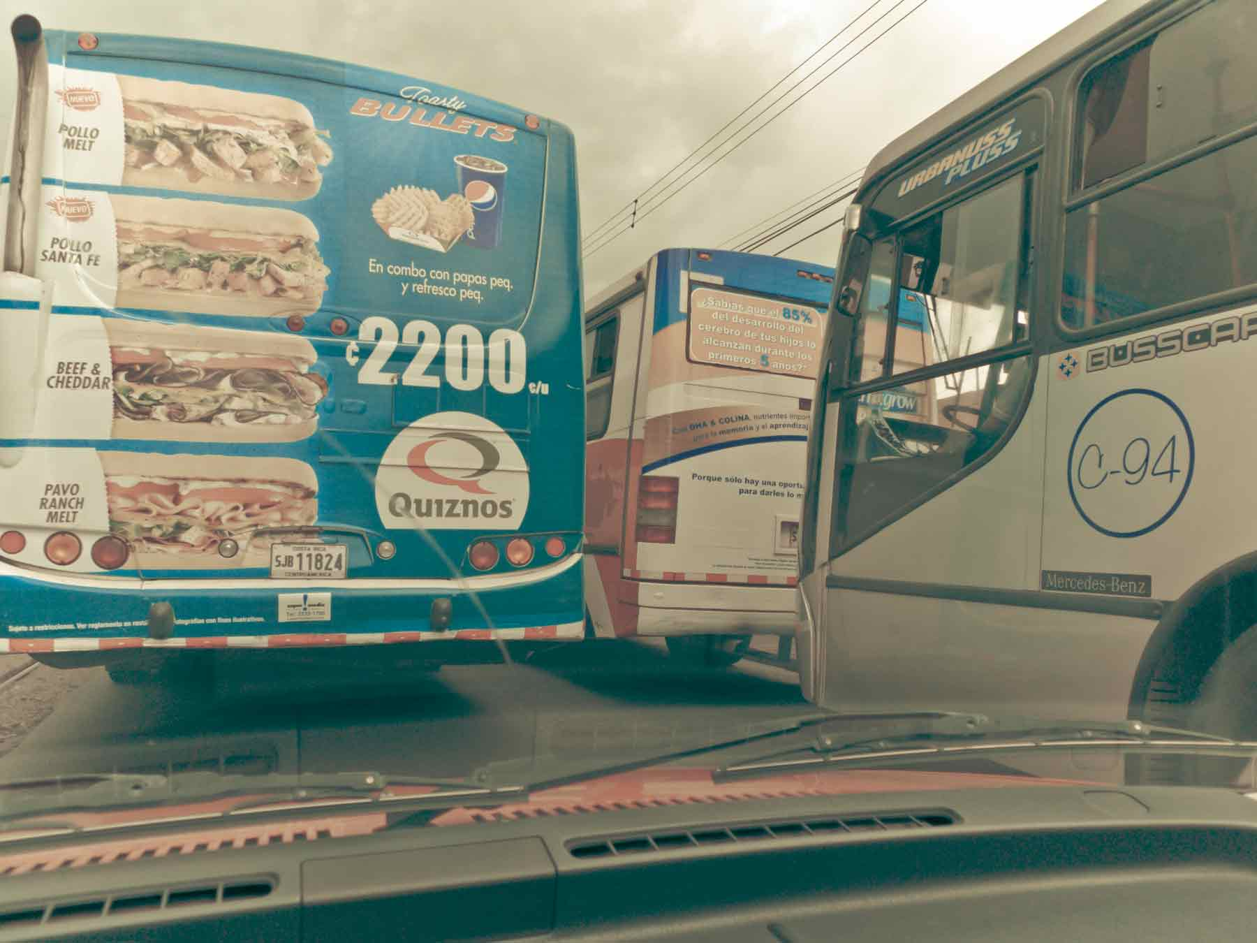 driving in the central valley, costa rica, surrounded by buses