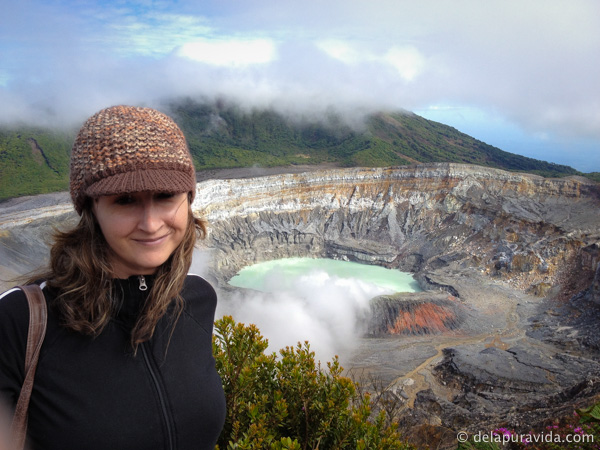 me standing in front of the chalky turquoise crater lake at poas volcano