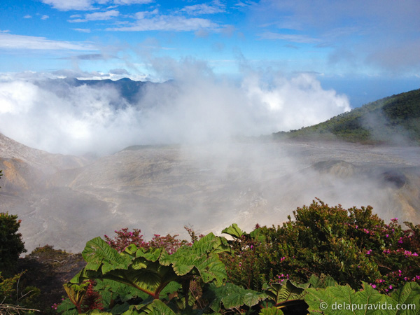Clouds and gases mixing together to the left of the active volcanic crater.