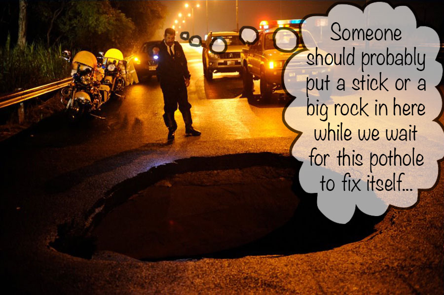 policeman shining his flashlight into big sinkhole in pan american highway in costa rica