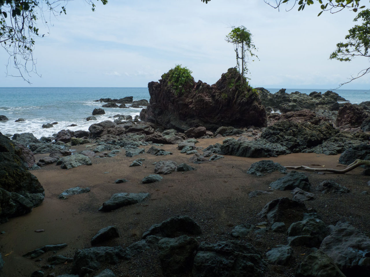 big rock formations on a sandy beach on the drake bay hike osa peninsula costa rica